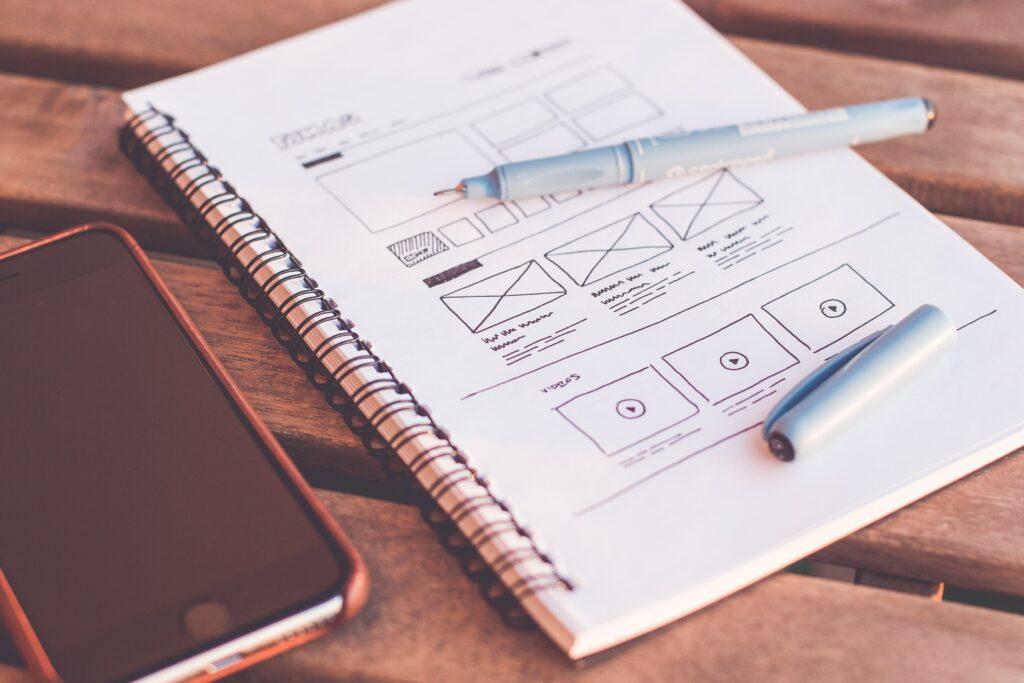 mobiltelefon och papper med ritad wireframe och penna